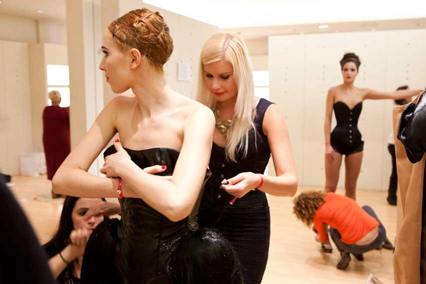 Maya Hansen ajustando el corsé de una modelo en el backstage del desfile Causa y Seducción, en el centro comercial Sexta Avenida de Madrid