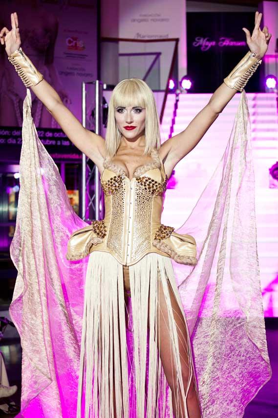 Modelo levantando los brazos triunfalmente en el desfile Causa y Seducción, en el centro comercial Sexta Avenida de Madrid