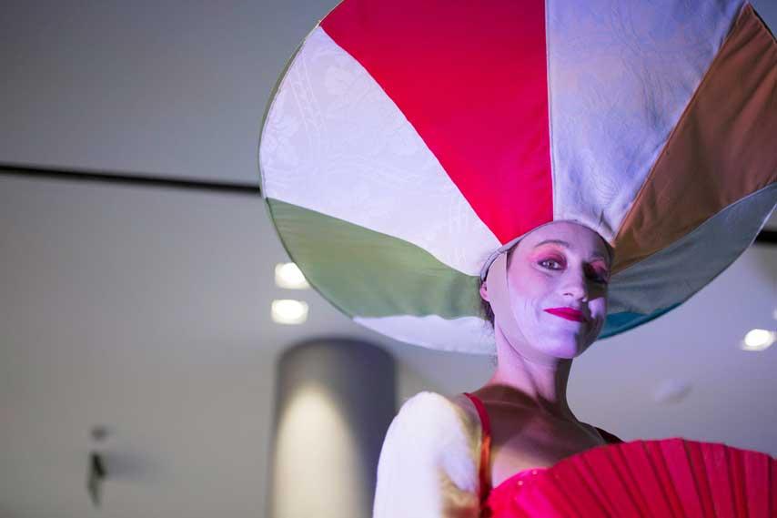 actriz con un tocado gigante y abanico sonriendo a los invitados de La Fira