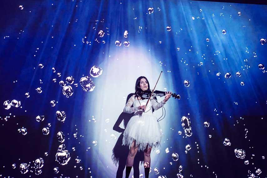 Violinista actuando en un espectáculo multimedia en la gala Carrefour Property y Carmila