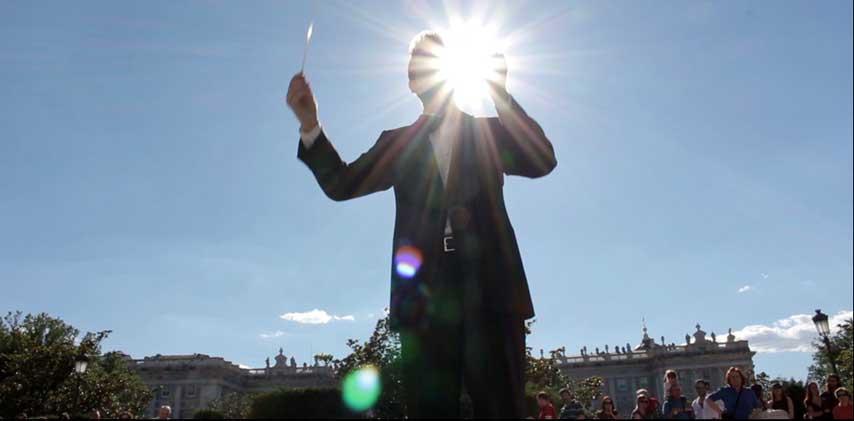 Director de orquesta dirigiendo al aire libre