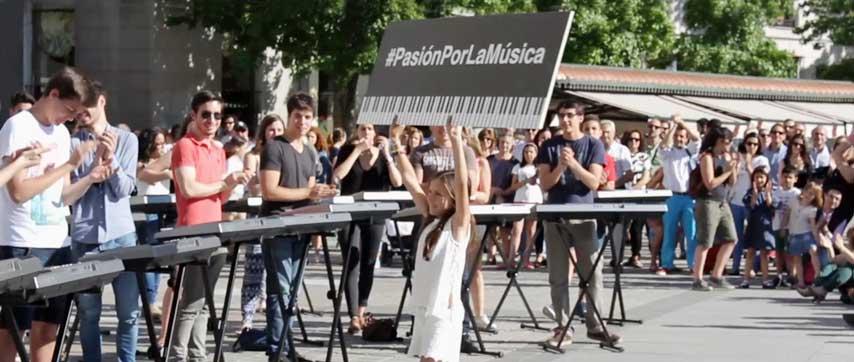 "niña mostrando un cartel con la leyenda ""Pasión por la música"" ante un grupo de espectadores"