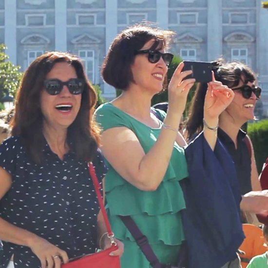 Mujeres sonriendo y tomando fotos en un flashmob en la Plaza de Oriente