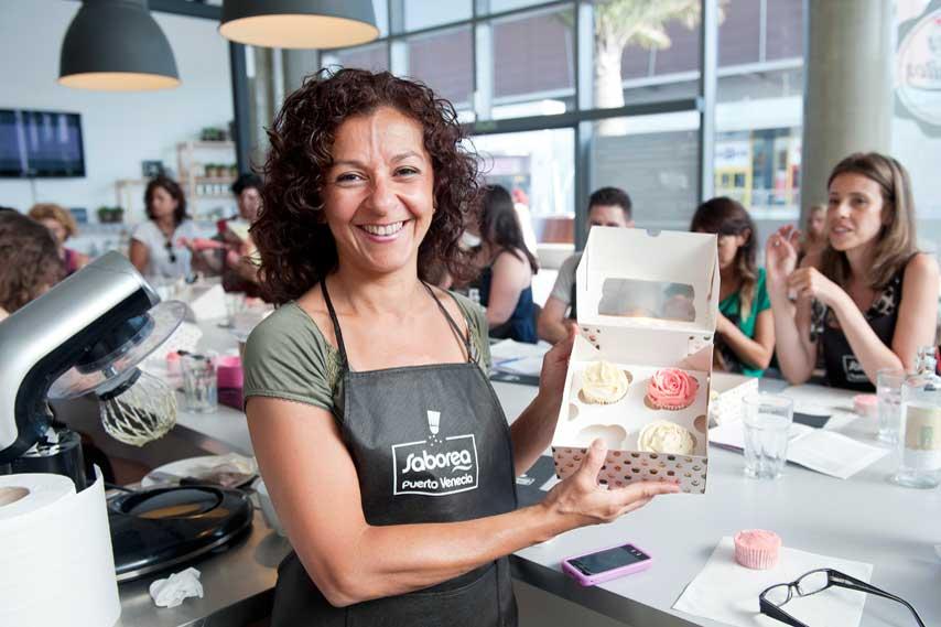 mujer sonriente enseñando cupcakes